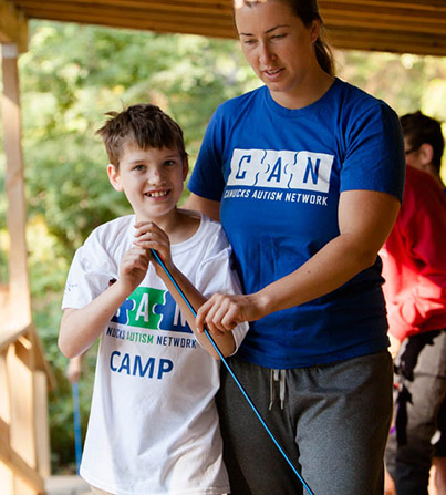 A young boy outside hanging out with a staff member of CAN.