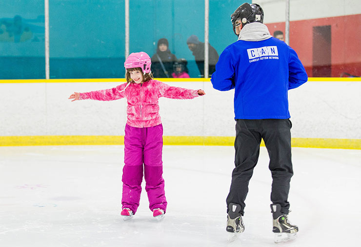 A child with autism ice skates under the watch of a support worker in our I CAN Skate program.