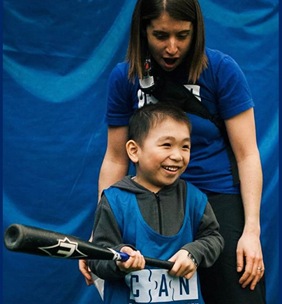 Program Director Stephanie Jull encourages a child with autism playing baseball at our annual Sports Day event.