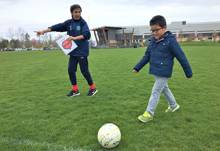 A young boy kicking a soccer ball with directions from a coach using visuals.